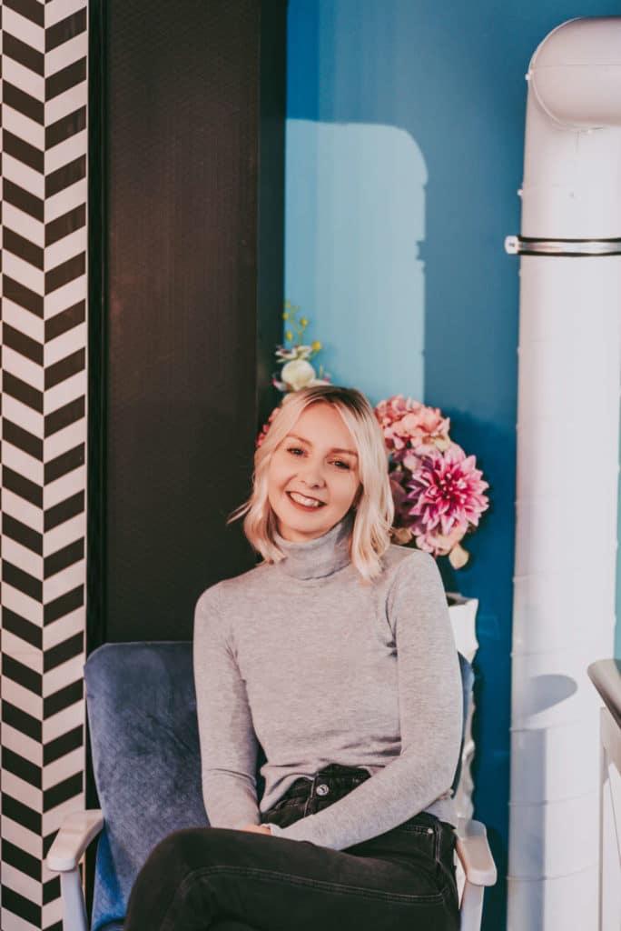 Essstoerung_Janina sitzt in einem Café und lächelt und bietet ein 1:1 Coaching an