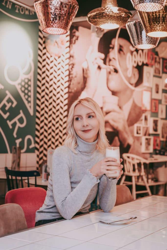 Essstoerungen_lebensleichter sitzt mit einem Chai Latte in einem Café und schaut in die Ferne
