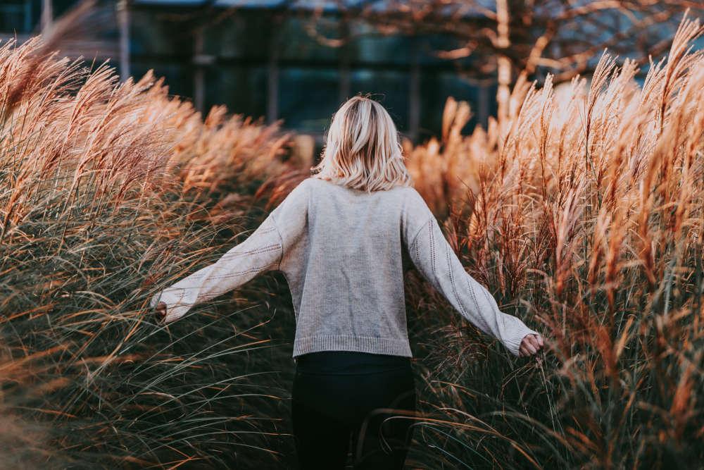 Essstoerungen_lebensleichter in der Abendsonne von hinten, wie sie durch das Gras läuft