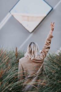 Essstoerungen_lebensleichter hält mit ihren Händen in Peace Zeichen in die Höhe und steht im Gras